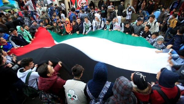 Students hold a Palestinian flag inside the Ain el-Hilweh refugee camp near Sidon, southern Lebanon, December 6, 2017. | Photo: Reuters