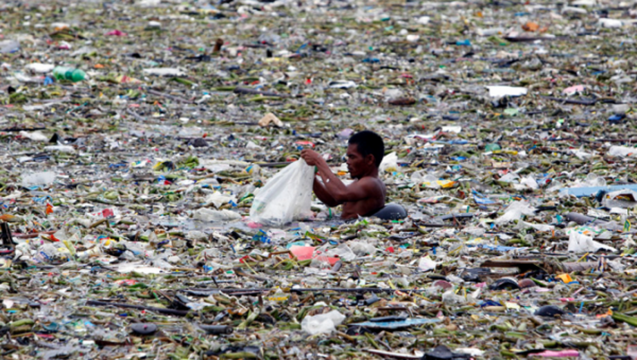A man collects plastic and other recyclable materials from debris in the waters of Manila Bay in Manila, Philippines, July 30, 2012. Mismanaged waste from land is the primary cause of the ocean plastics crisis. | Photo: Reuters